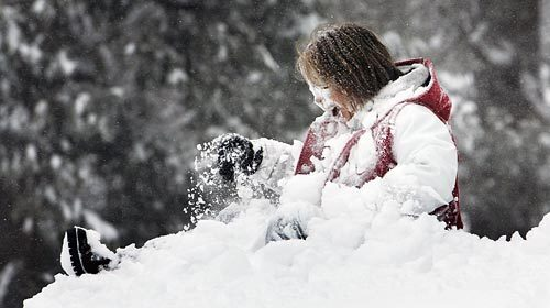 Angie Armenta of Upland emerges from a snowbank after sledding down a hill on Mt. Baldy.