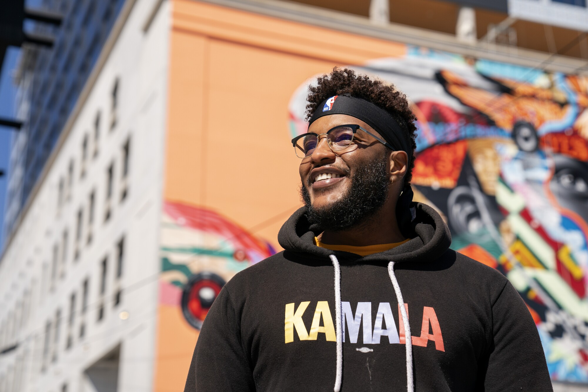 "A closeup of a man wearing a hoodie that says ""Kamala."""