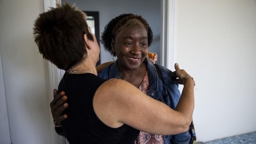 Patricia Williams, right, gets a hug from Heidi Roberts as she and other tenants move into their new home along Wall Street in South Los Angeles on Monday.