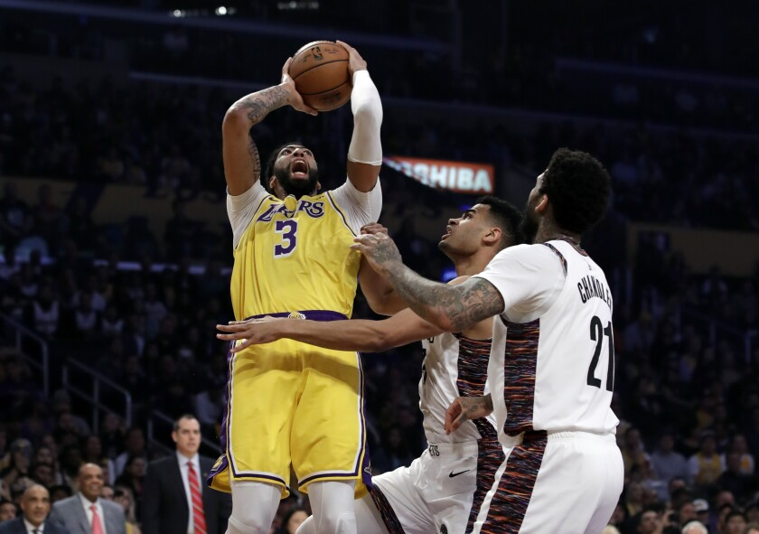 The Lakers' Anthony Davis shoots over two Nets defenders during both teams' last game played before the suspension of play across the NBA.