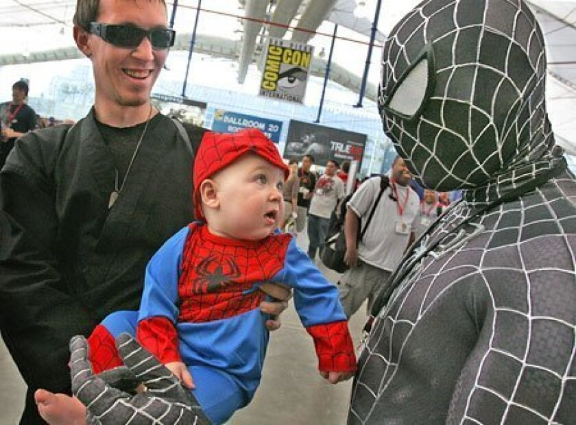 Tony Daniel of Santee held his costumed son, Tristan, as the 8-month-old came face-to-face yesterday with a full-grown version of comic book hero Spider-Man at the 40th annual Comic-Con at the San Diego Convention Center. The event in downtown San Diego brought big crowds and long lines. (Howard Li