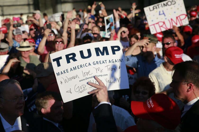 Republican presidential candidate Donald Trump, center, holds up a sign after autographing it during a rally at the Sacramento International Jet Center, Wednesday, June 1, 2016, in Sacramento, Calif. (AP Photo/Jae C. Hong)