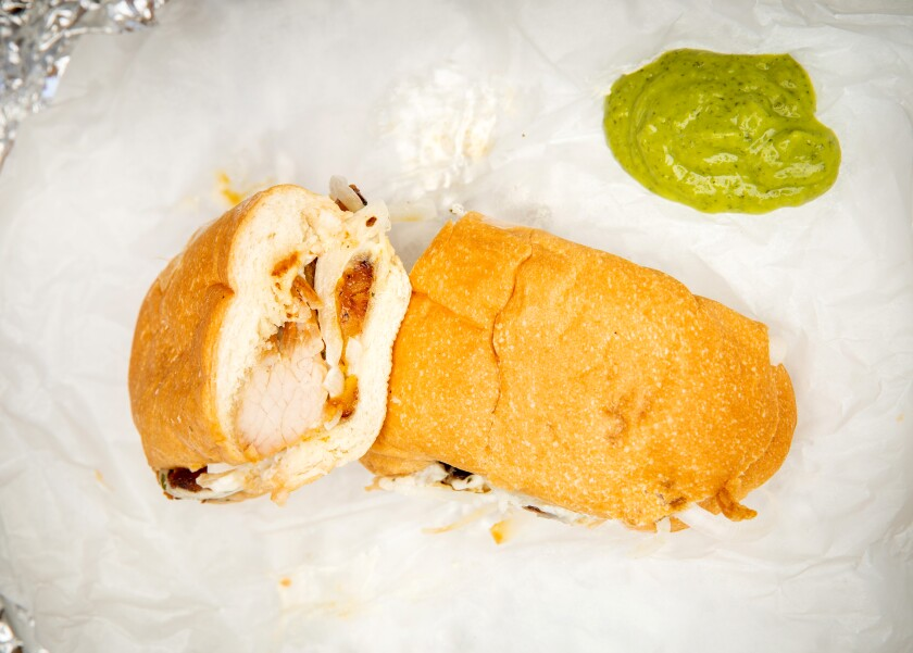 A fried pork sandwich, to take away, with a green sauce made from coriander, jalapenos, garlic, lime juice, avocado.