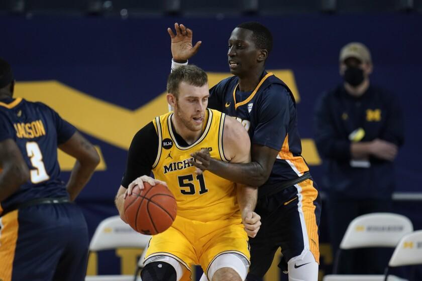 Michigan forward Austin Davis (51) drives on Toledo center Jonathan Komagum (35) in the first half of an NCAA college basketball game in Ann Arbor, Mich., Wednesday, Dec. 9, 2020. (AP Photo/Paul Sancya)