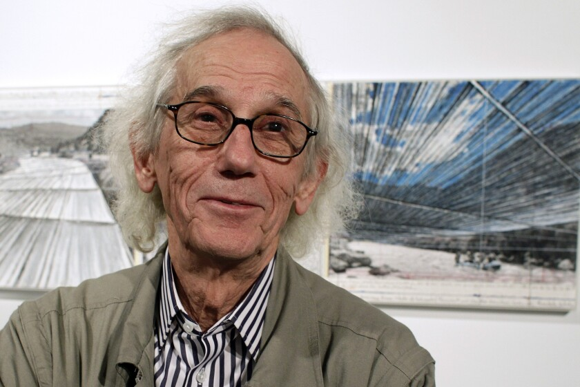 "A file photo from 2013 shows artist Christo posing in front of his proposed ""Over the River"" project in Denver."