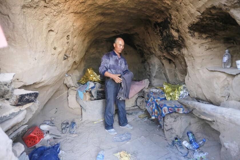 مردی در غاری در میان پتوها و بطری های آب مایلار دور ریخته ایستاده است.