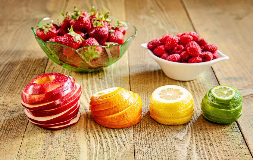 Stacks of sliced apple, orange, lemon, lime with two bowls, one with strawberries and the other with raspberries.