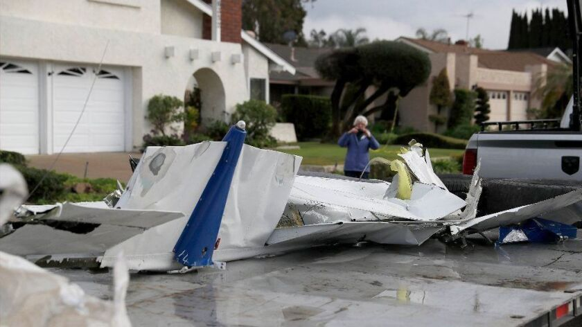 A woman takes a photo of airplane parts that landed on her property as workers remove wreckage after a crash of a Cessna after it crashed in Yorba Linda on Sunday, killing the pilot and four people inside a home.