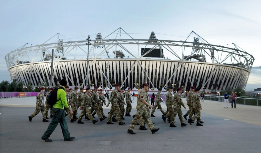 """FILE- In this Aug. 12, 2012, file photo, ,embers of the British military march by Olympic Stadium before the Closing Ceremony of the 2012 Summer Olympics in London. The players' association says Major League Baseball has given up plans to play regular-season games in the British capital in 2017. """"T"""