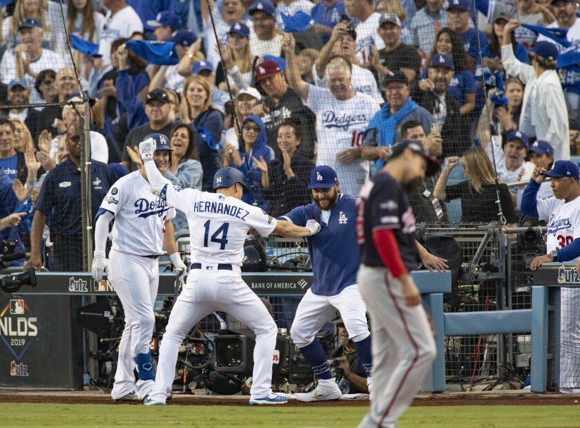 Dodgers left fielder Enrique Hernandez (14) celebrates his solo homer with Joc Pederson (31) and Russell Martin in the second inning of Game 5 of the NLDS at Dodger Stadium on Wednesday.