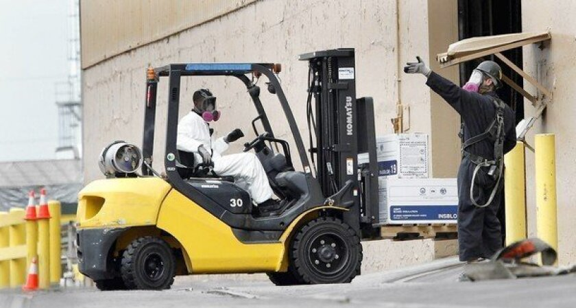 Wearing breathing devices, employees move boxes at the Exide battery recycling plant in Vernon. State officials suspended operations at the plant in April, citing emissions of arsenic as a health risk to 110,000 people in surrounding communities. The plant has also discharged harmful quantities of lead.