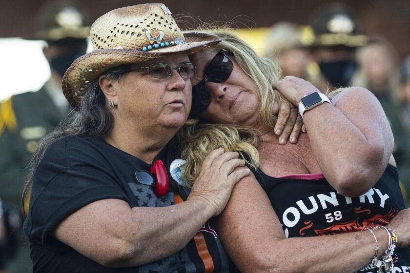 Route 91 Harvest festival shooting survivors Sue Ann Cornwell, left, of North Las Vegas, and Alicia Mierke of Henderson attend the annual 1 October Remembrance Ceremony at the Clark County Government Center on Friday, Oct. 1, 2021, in Las Vegas. (Bizuayehu Tesfaye/Las Vegas Review-Journal via AP)