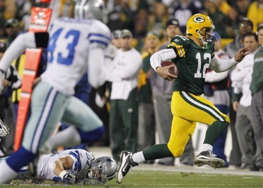 Green Bay Packers quarterback Aaron Rodgers (12) breaks away from Dallas Cowboys linebacker Keith Brooking (51) for a first down during the first half of an NFL football game Sunday, Nov. 7, 2010, in Green Bay, Wis. (AP Photo/Mike Roemer)