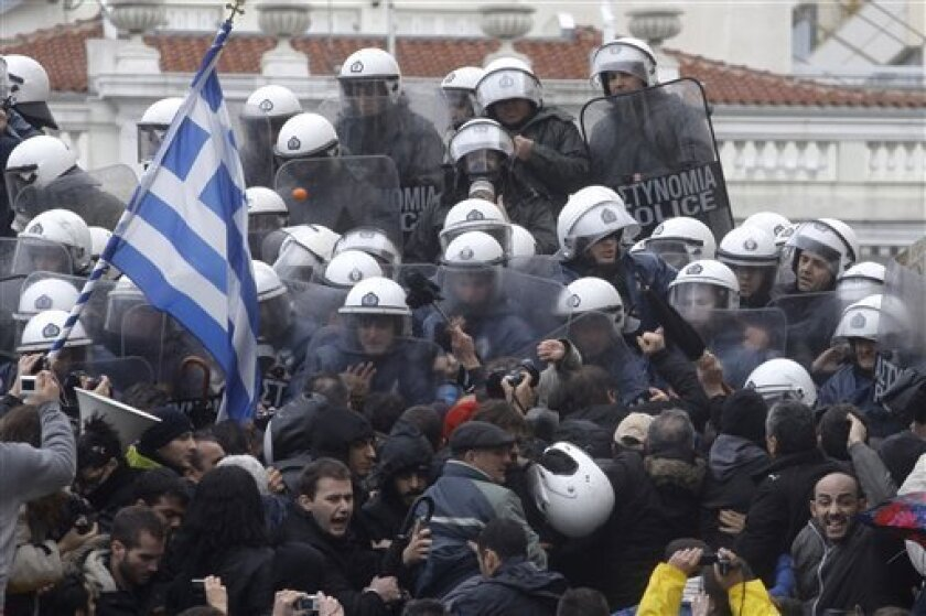 Riot Police push back protestors, one waving the Greek flag, who try to enter at the Parliament building at Athens' main Syntagma square, during a 24-hour strike on Tuesday, Feb. 7, 2012. A general strike against the impending cutbacks stopped train and ferry services nationwide, while many schools and banks were closed and state hospitals worked on skeleton staff. (AP Photo/Petros Giannakouris)