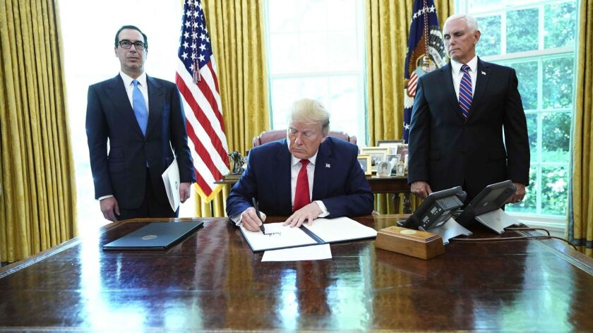 "President Trump signs ""hard-hitting"" sanctions on Iran's supreme leader as Vice President Mike Pence, right, and Treasury Secretary Steven Mnuchin look on at the White House on Monday."