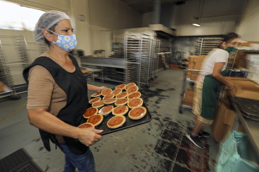 Guadalupe Valdovinos, left, packs pies at 27th Street Bakery Shop.