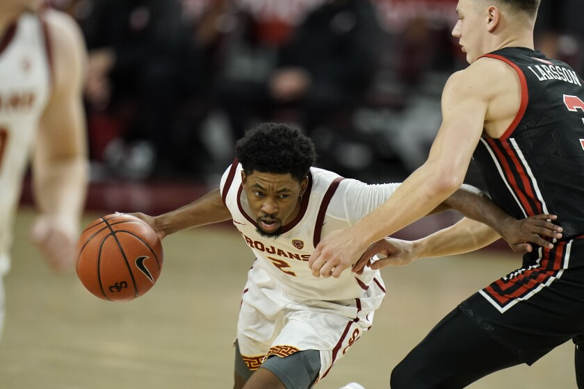 Southern California's Tahj Eaddy, left, is pressured by Utah's Pelle Larsson during the second half of an NCAA college basketball game, Saturday, Jan. 2, 2021, in Los Angeles. USC won 64-46. (AP Photo/Jae C. Hong)