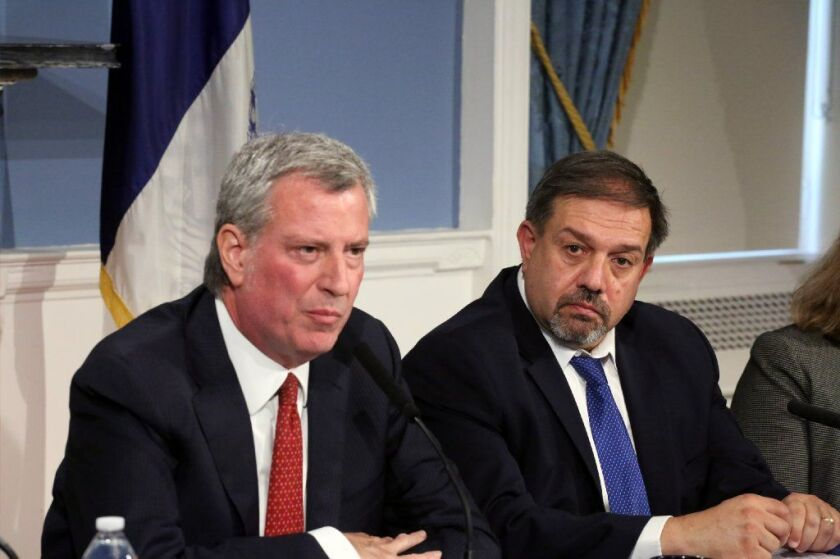 Mayor de Blasio (left) and NYCHA general manager Vito Mustaciuolo (right) discuss a consent degree to reform the agency at a City Hall press conference in June.