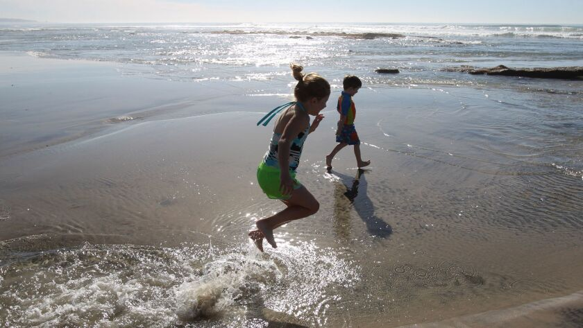 Kids play in puddles left by a low tide in Solana Beach.
