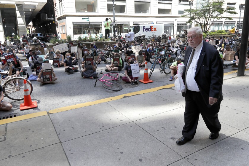 A pedestrian walks past protesters sitting on La Salle Street in front of Chicago's City Hall, Wednesday, June 17, 2020, demanding that Mayor Lori Lightfoot enact the ordinance for an all-elected Civilian Police Accountability Council, CPAC. (AP Photo/Charles Rex Arbogast)