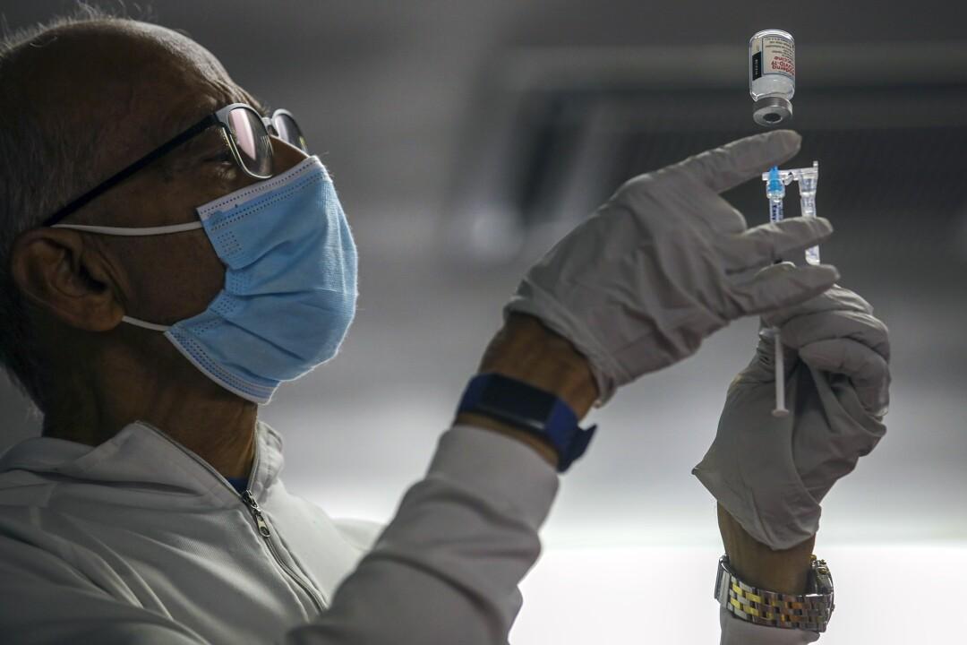 Dr. Narendra Parson prepares a COVID-19 vaccine