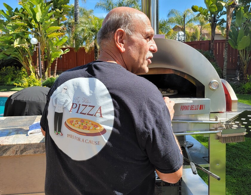 Willie DePascale of Chula Vista cooks pizzas in his backyard oven for charity.