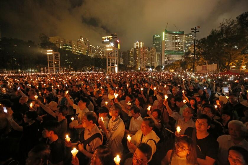 ARCHIVO - En esta imagen de archivo del 4 de junio de 2019, miles de personas asisten a una vigilia con velas en el Parque Victoria de Hong Kong en memoria de las víctimas de la brutal represión militar del gobierno chino tres décadas antes contra los manifestantes en la plaza de Tiananmen, Beijing. Nueve activistas y exlegisladores hongkoneses fueron condenados a penas de hasta 10 meses de cárcel el miércoles 15 de septiembre de 2021 por su papel en la vigilia prohibida de 2020. (AP Foto/Kin Cheung, Archivo)