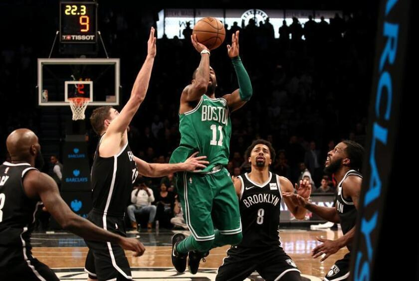 Boston Celtics guard Kyrie Irving (C) shoots over Brooklyn Nets defenders in the second half of their NBA basketball game at Barclays Center in Brooklyn, New York. EFE