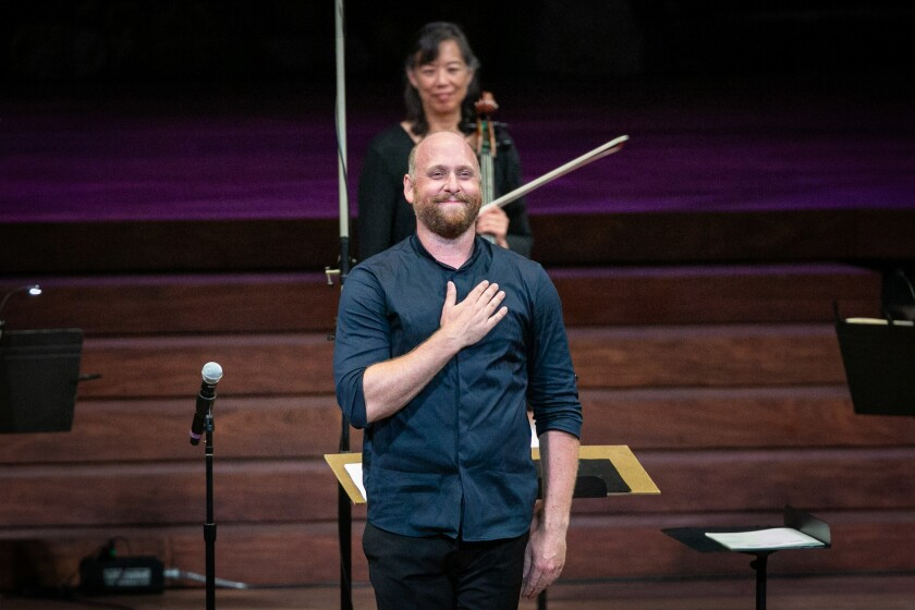 Christopher Rountree, wearing a blue shirt, places his hand over his chest as he acknowledges the audience