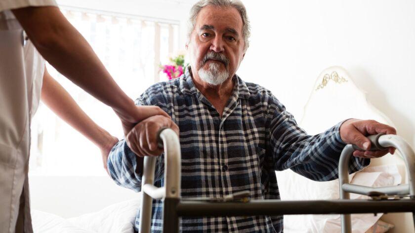 Female doctor standing by senior man holding walker in nursing home