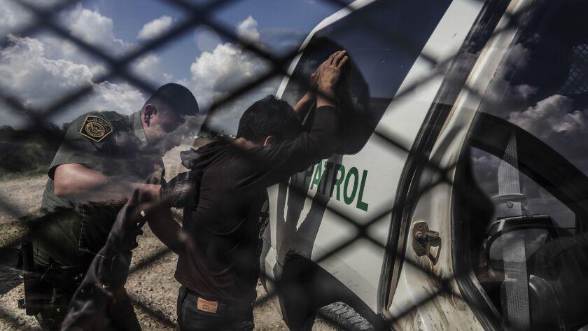 MCCALLEN, TEXAS, MONDAY, JUNE 25, 2018 - Border patrol agent Rene Cisneros frisks Tom de Huachac, 33