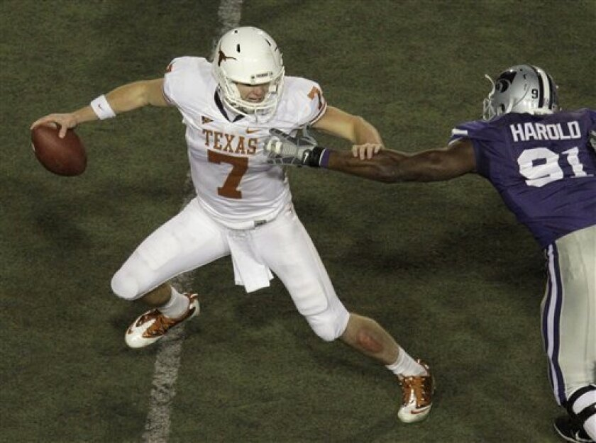 Texas quarterback Garrett Gilbert (7) tries to escape as he drops back to pass under pressure from Kansas State defensive end Brandon Harold (91)during the second quarter of a college football game Saturday, Nov. 6, 2010 in Manhattan, Kan. (AP Photo/Charlie Riedel)