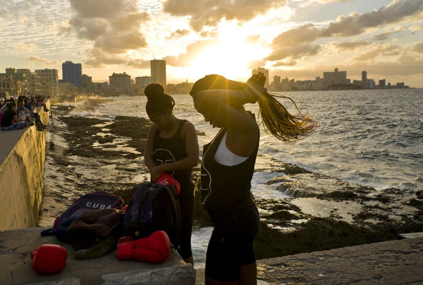 Las boxeadoras Idamerys Moreno (i) y Legnis Cala se preparan para una sesión de fotos en el Malecón de La Habana, en Cuba. Moreno entrena al menos dos horas al día después de salir de su trabajo; pelea tanto con hombres como con mujeres.