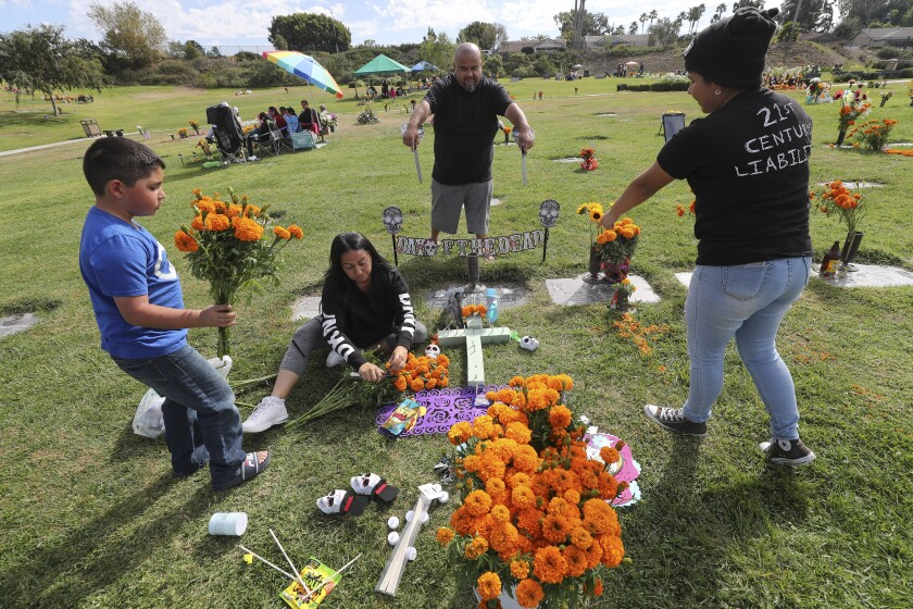 Anthony Jacquez, 10, holds marigold flowers as he, his mother Maria Duran (sitting), sister Angelica Jacquez, 17, and uncle Estevan Duran decorate the the graves of their parents and grandparents, Juan and Maria Duran, during the Dia de los Muertos celebration at Eternal Hills Memorial Park on Saturday in Oceanside.