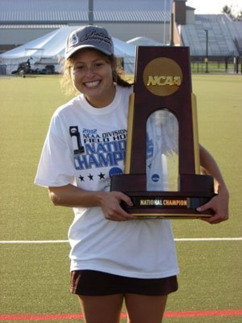 helsea Yogerst hoists the NCAA trophy after Tufts victory in the national championship game.