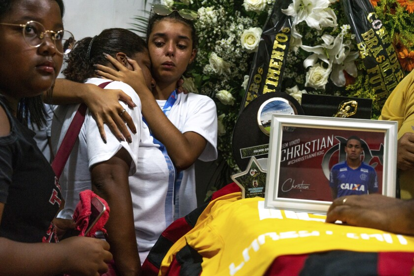 Friends and relatives of the late Christian Esmerio Candido attend his burial at a cemetery in Rio de Janeiro, Brazil, Sunday, Feb. 10, 2019. Hundreds of grief-stricken people attended the funeral of the 15-year-old, one of 10 young soccer players killed in a fire at the training ground of Brazilian soccer club Flamengo on Friday.