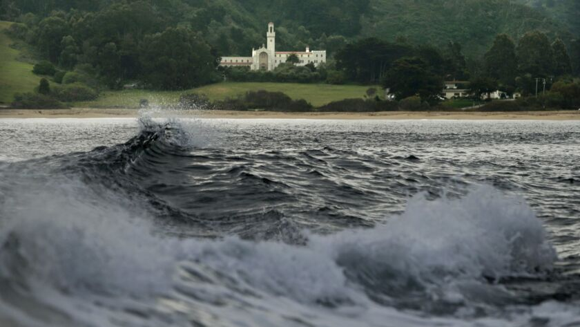 Waves break at Monastery Beach, with the Chapel of the Carmelite Monastery in the background, in Carmel in this 2013 file photo. A Scotsman was reported missing from the treacherous beach last week, but officials now think the man faked his own death.