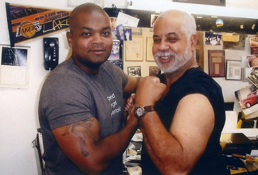 At his L.A. barbershop, Lawrence Tolliver II has some fun with Lawrence III, who was a Cal State L.A. grad, a veteran and a Houston police trainee.