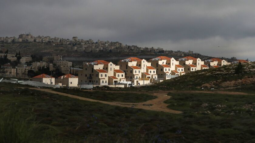 The Jewish settlement of Neve Yaakov, foreground, in east Jerusalem and Israel's barrier separating the Palestinian neighborhood of al-Ram, background, in the West Bank.