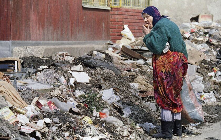 FILE - In this April 6, 1993, file photo, a woman eats a bit of food she found in a pile of trash on the street in Sarajevo. The Serb siege of Sarajevo went on longer than the 900-day siege of Leningrad in World War II. (AP Photo/Michael Stravato, File)