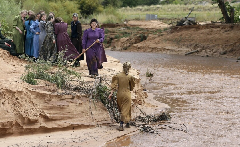 People search along a stream after a flash flood in Colorado City, Ariz.