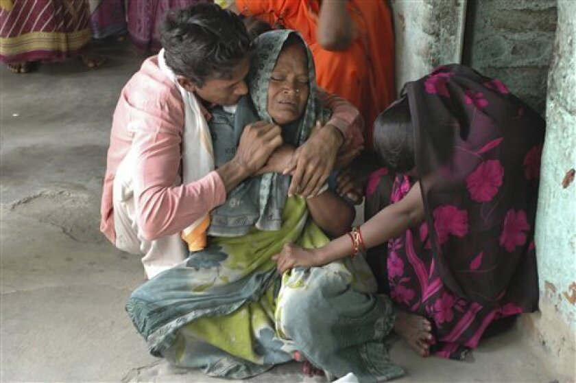 Relatives, mourn near body, unseen, of a person suspected of having died after consuming illicitly brewed liquor in Ahmadabad, India, Wednesday, July 8, 2009. Police say 43 people have died in western India days after drinking home-brewed liquor that was apparently toxic. (AP Photo/Ajit Solanki)