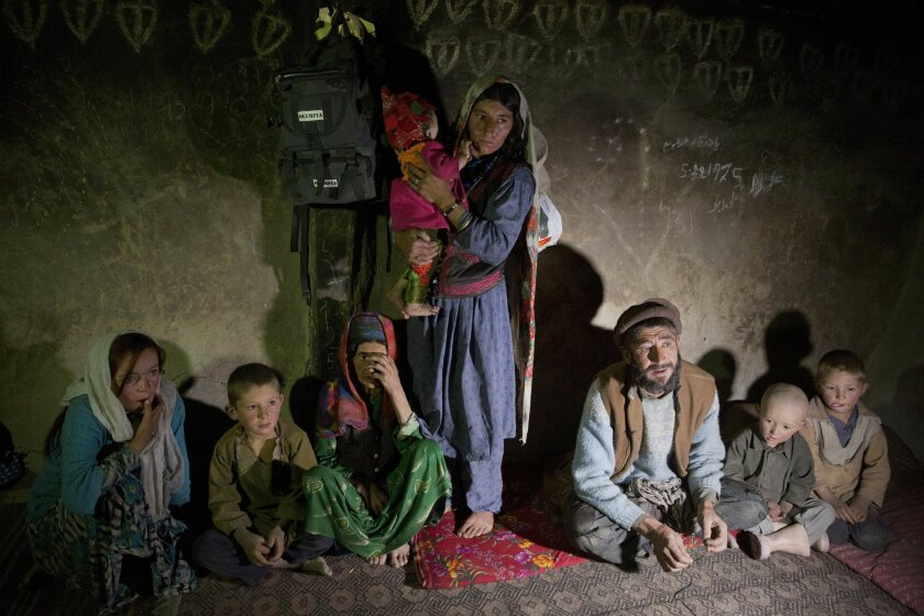 In this Aug. 18, 2016 photo, Saeed Beg, third right, and his family sit in their home during an interview with The Associated Press, in Sarkand village, Wakhan district of Badakhshan province, far northeastern Afghanistan. Beg and his family live in a two-room mud house with no electricity or runni