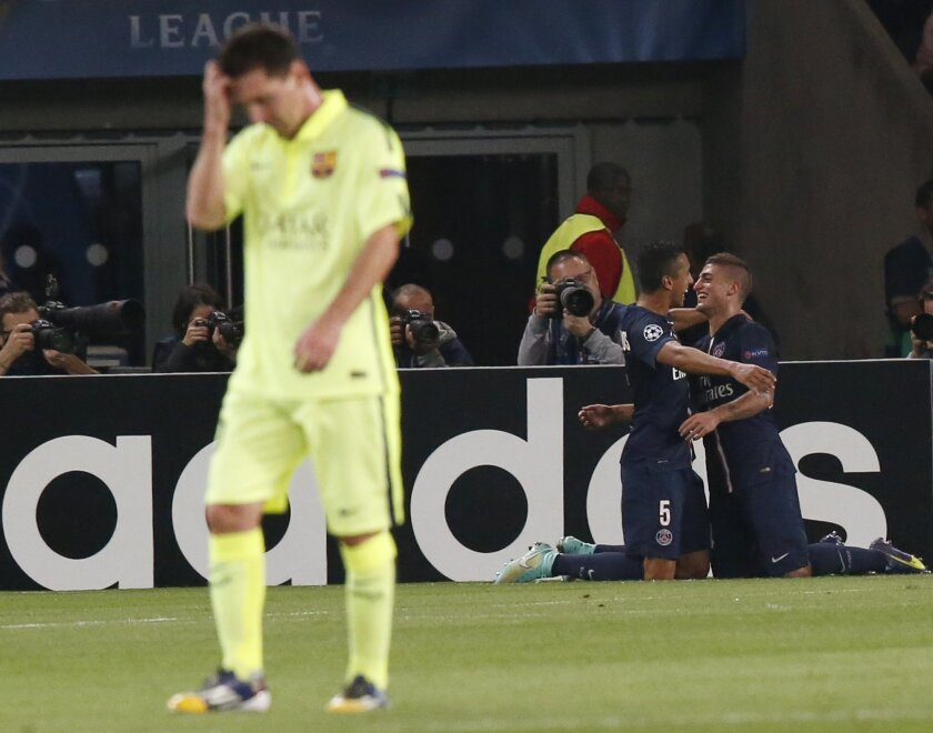 PSG's Marco Verratti, right, is congratulated by PSG's Marquinhos after scoring his side's 2nd goal, while Barcelona's Lionel Messi, left, passes by during the Champions League Group F soccer match between Paris Saint German and Barcelona at Parc des Princes stadium in Paris, France, Tuesday, Sept. 30, 2014. (AP Photo/Michel Euler)