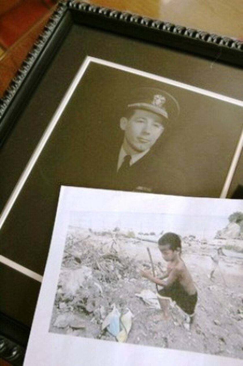 Photos show Leon Cooper in his Navy uniform and a child playing in the trash on Tarawa.
