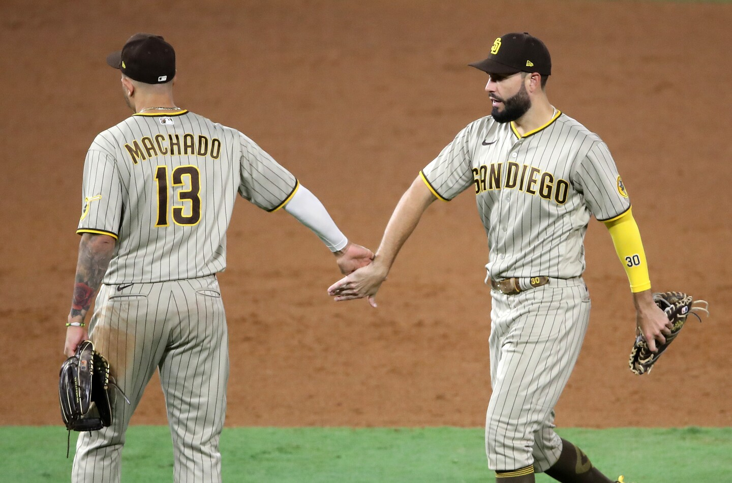 ANAHEIM, CALIFORNIA - SEPTEMBER 02: Manny Machado #13 congratulates Eric Hosmer #30 of the San Diego Padres after defeatig the Los Angeles Angels 11-4 in a game at Angel Stadium of Anaheim on September 02, 2020 in Anaheim, California. (Photo by Sean M. Haffey/Getty Images)
