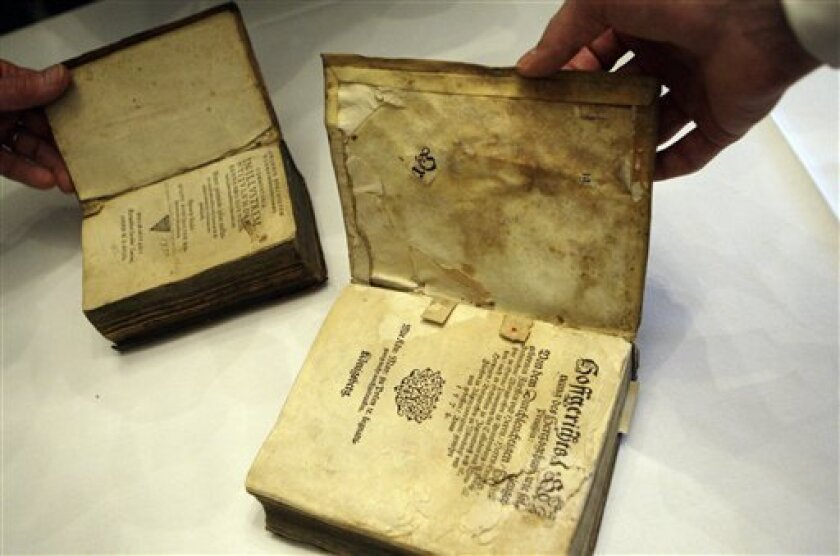 Two 16th century books are seen on display during a news conference at the National Archives Building in Washington, Tuesday, Oct. 6, 2009. Robert Thomas returned the two 400-year-old law books he took as souvenirs from a German salt mine vault in the closing months of World War II. (AP Photo/ Haraz N. Ghanbari)