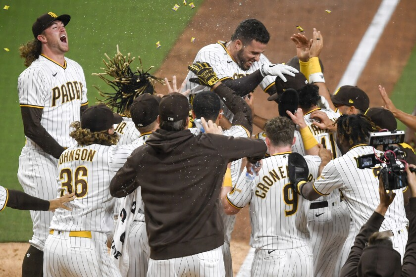 The Padres' Victor Caratini is greeted at the plate by teammates after hitting a walk-off, two-run home run
