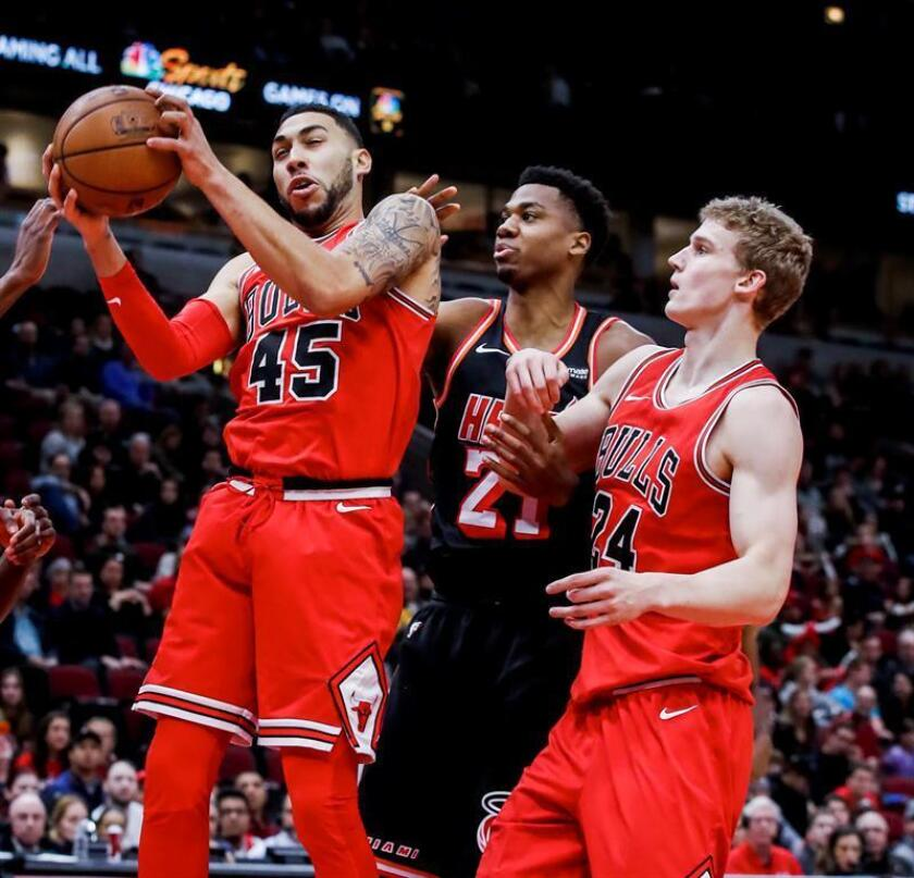 Chicago Bulls guard Denzel Valentine (L) pulls down a rebound in front of Miami Heat center Hassan Whiteside (C) and Chicago Bulls forward Lauri Markkanen of Finland (R) in the first half of their NBA game. EFE/Archivo