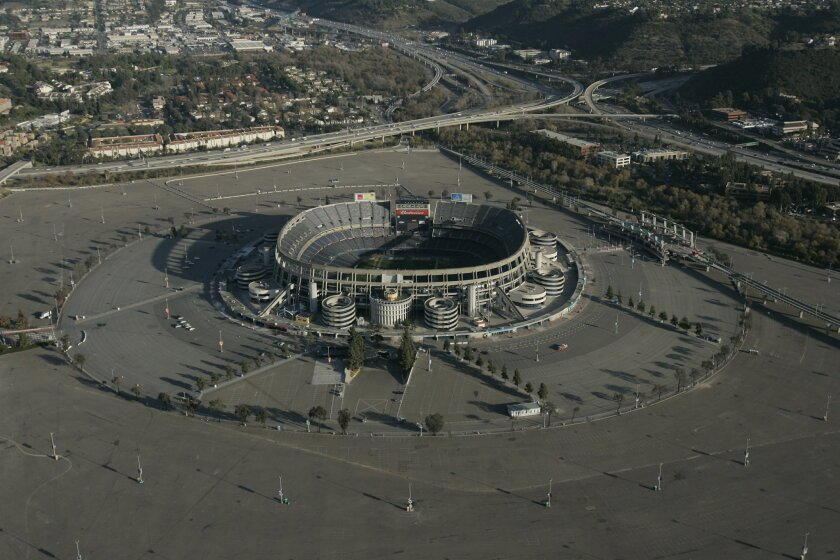Aerial view of Qualcomm Stadium with its surrounding expansive parking lot. Interstate 8 is to the right. Interstate 15 above and to the left of stadium.